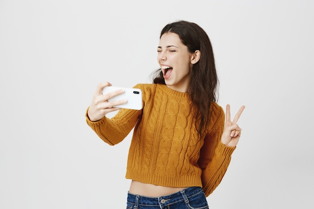 Chica morena atractiva tomando selfie en smartphone Foto gratis