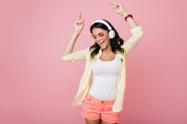 Chica morena delgada inspirada en gafas de sol divertidas bailando y agitando las manos. riendo a mujer joven de pelo oscuro con camisa amarilla disfrutando de la música en auriculares con los ojos cerrados. Foto gratis