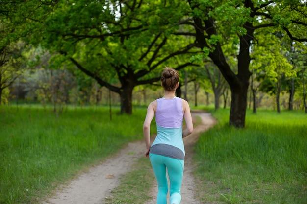 Chica morena de deportes para correr en el parque. bosque verde Foto Premium