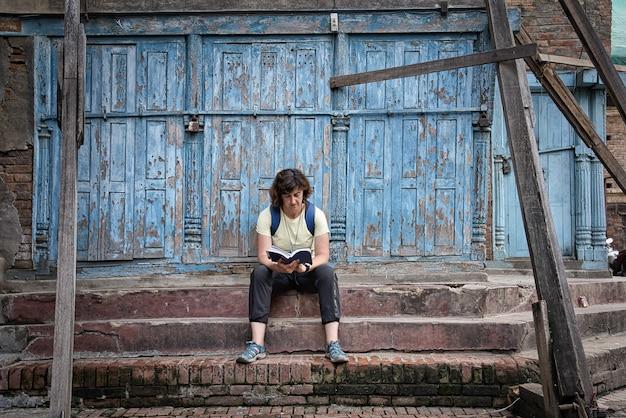 Chica morena occidental con mochila sentado en los escalones de piedra marrón en la calle leyendo una guía de viaje con una hermosa puerta de madera pelada azul. Foto Premium
