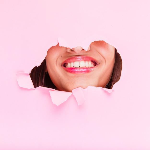 Chica morena posando a través de agujero de papel Foto gratis
