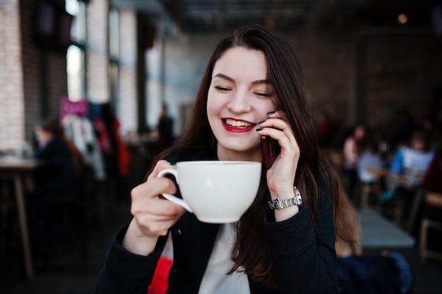 Chica morena sentada en la cafetería con una taza de capuchino y hablando de teléfono móvil. Foto Premium