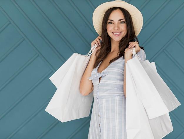 Chica morena con sombrero y muchas redes comerciales Foto gratis