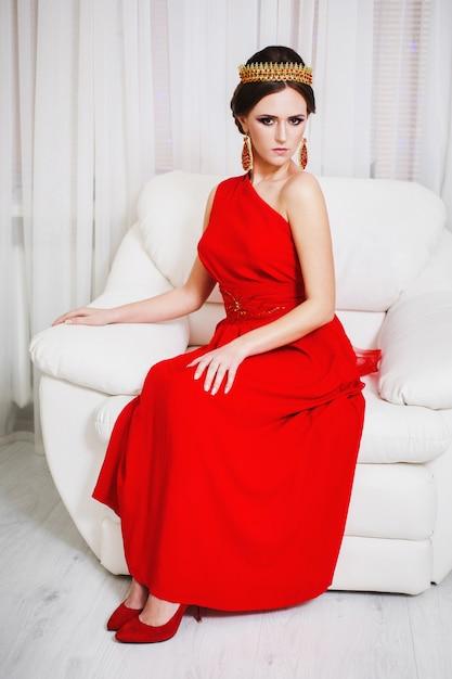 Chica morena con un vestido rojo con un hermoso peinado, aretes de cuentas y una corona en la cabeza y maquillaje brillante. estilo femenino mujer misteriosa. Foto Premium