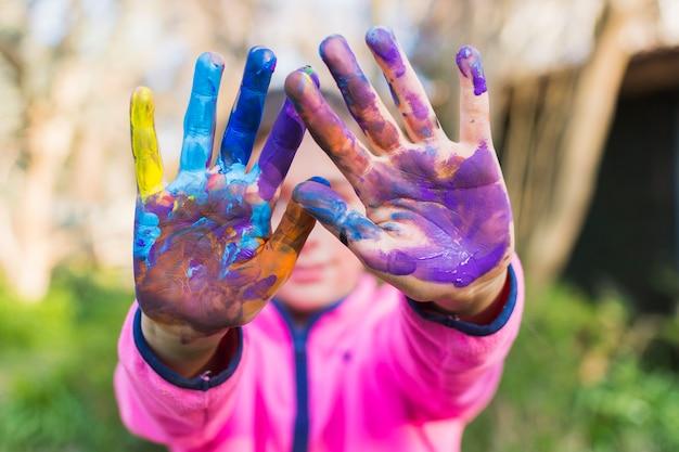 Chica mostrando sus coloridas manos pintadas Foto gratis