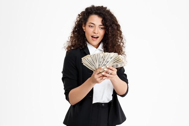 Chica de negocios rizado alegre con dinero Foto gratis