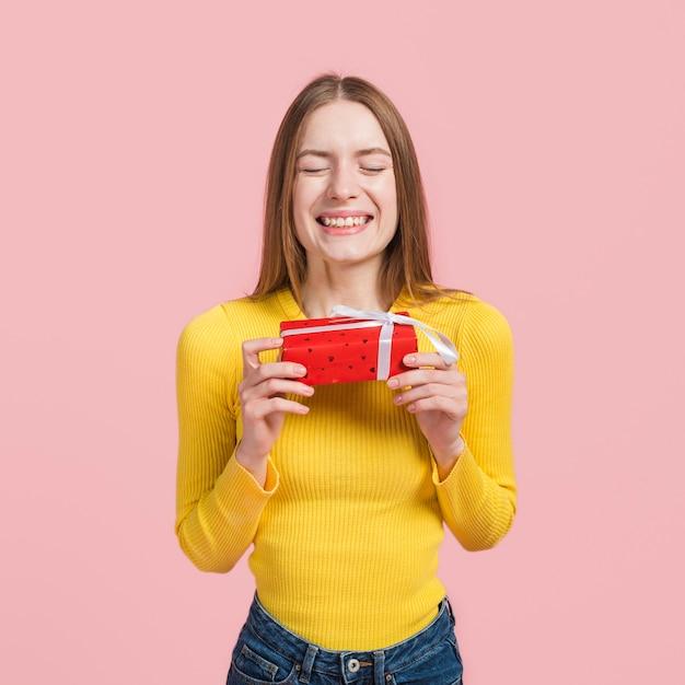Chica nerviosa por abrir un regalo Foto gratis