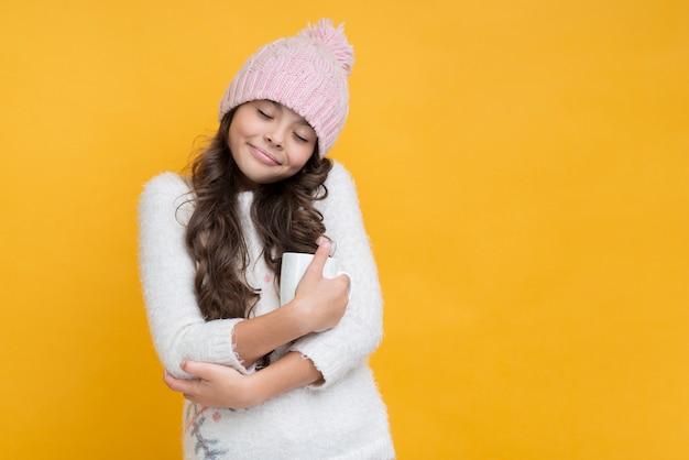 Chica con los ojos cerrados abrazando una taza de chocolate caliente Foto gratis
