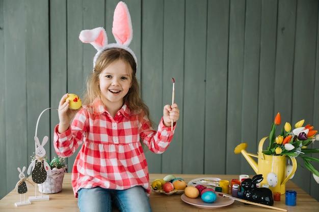 Chica en orejas de conejo pintando huevo para pascua Foto gratis