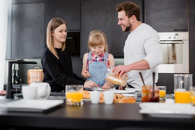 Chica con padres preparando el desayuno Foto gratis