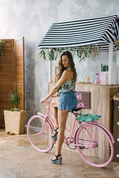 Chica en pantalones cortos de mezclilla con piernas largas en una bicicleta rosa cerca del bar Foto Premium