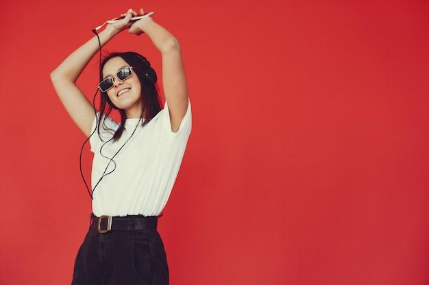 Chica en una pared roja con auriculares Foto gratis