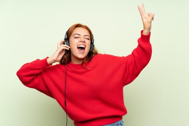 Chica pelirroja adolescente con suéter sobre verde aislado escuchando música con auriculares Foto Premium