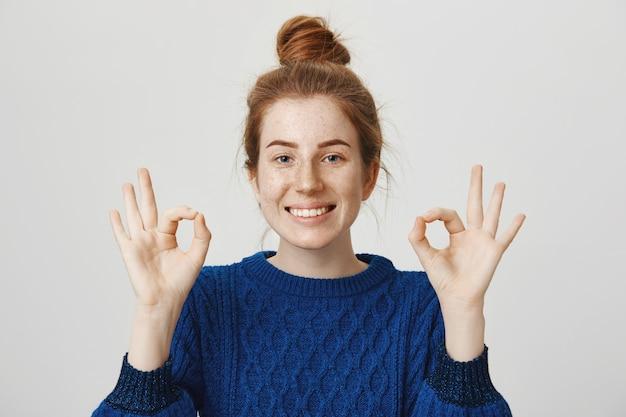Chica pelirroja alegre sonriendo, mostrando bien en aprobación, asegura que todo está bien Foto gratis