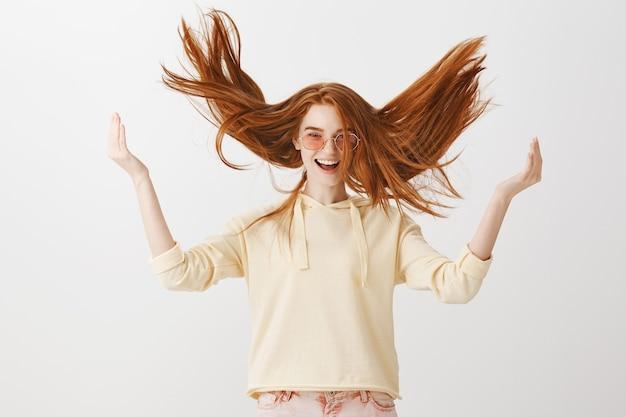 Chica pelirroja hermosa despreocupada tirando cabello en el aire Foto gratis