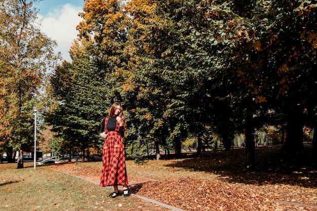 Chica con el pelo largo y castaño en el parque de otoño chica con vestido largo escocés rojo Foto Premium