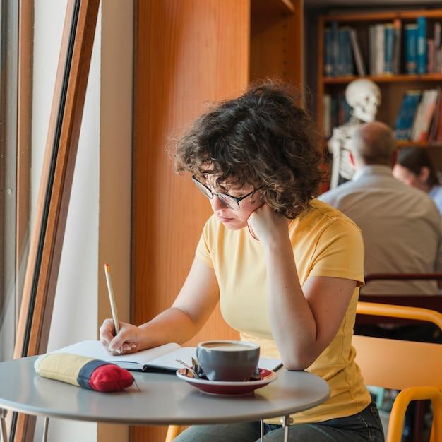 Chica pensativa adolescente escribiendo en el bloc de notas cerca de ...