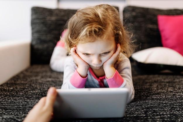 Chica pensativa viendo video en tableta Foto gratis