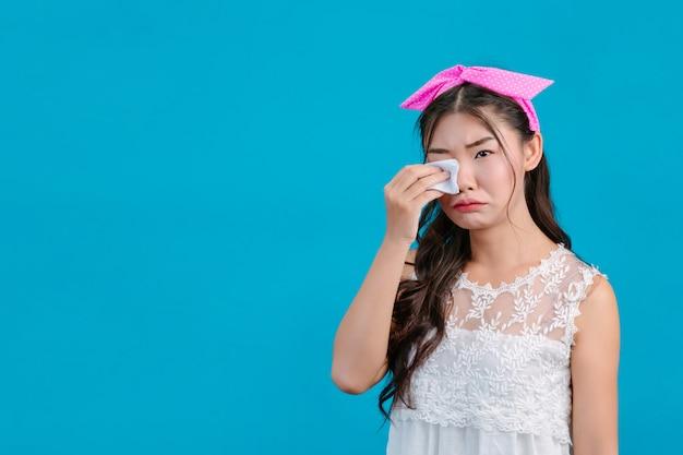 Chica con pijama blanco usando papel de seda en la cara en un azul. Foto gratis