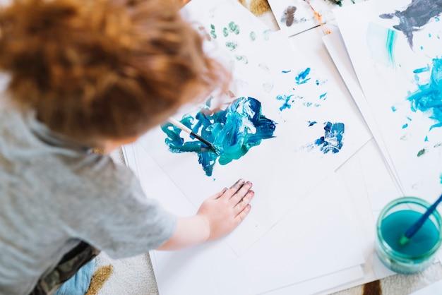 Chica con pincel pintando sobre papel y sentada en el piso Foto gratis