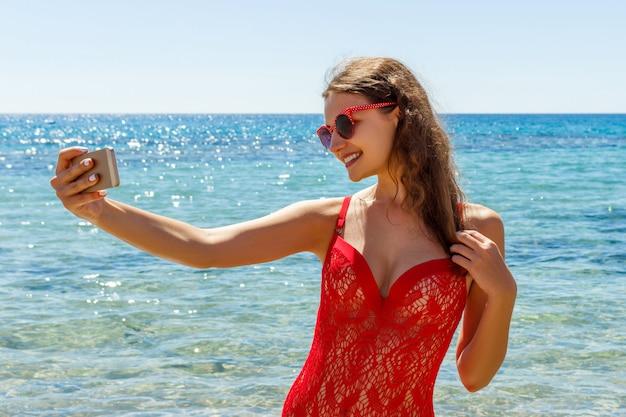 Chica en la playa con un teléfono celular haciendo selfie en día soleado Foto Premium
