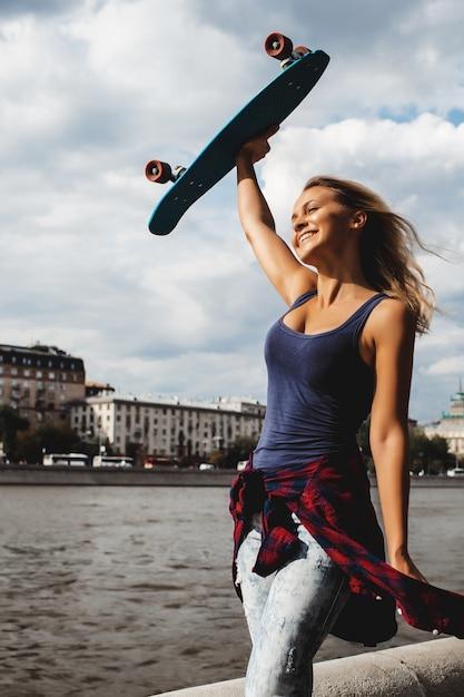 Chica posando con tabla de skate Foto gratis