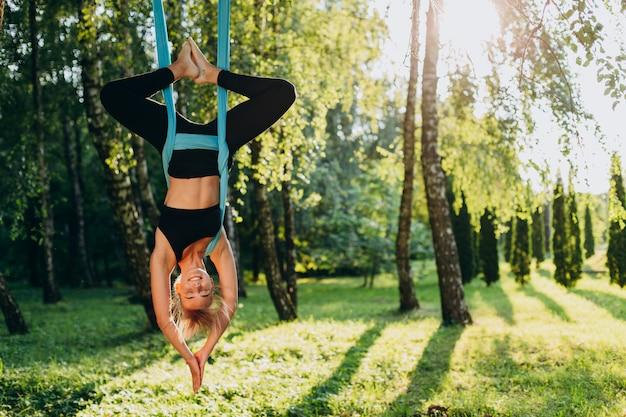 Chica practicando yoga mosca en el árbol colgar boca abajo. Foto Premium