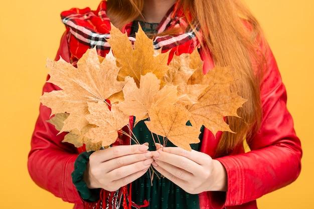 Chica de primer plano con hojas amarillas Foto gratis