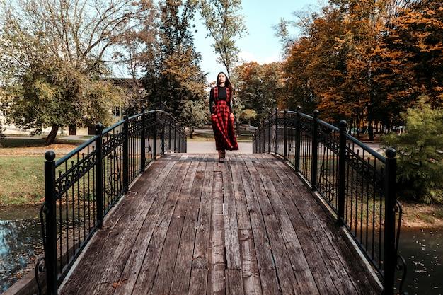 Chica en puente con vestido largo escocés rojo chica con cabello largo y castaño en el parque otoño Foto Premium