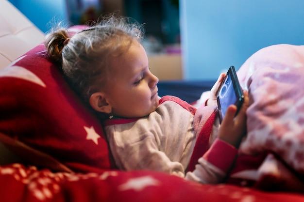 Chica que pone el juego de teléfono inteligente en la cama Foto gratis