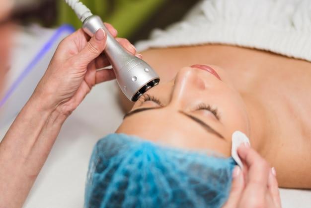 Chica recibiendo tratamiento facial en salón de belleza Foto gratis