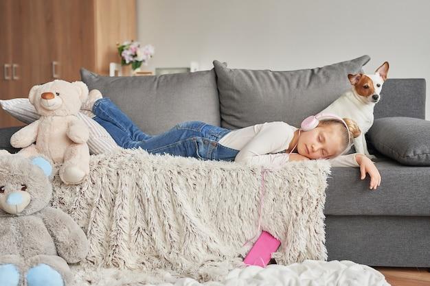 Chica recostada en el sofá con auriculares, escuchando música con su teléfono inteligente Foto Premium