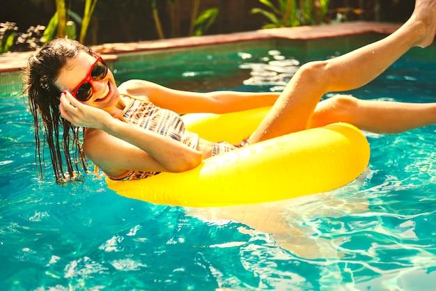 Chica refrescándose en una piscina Foto Premium