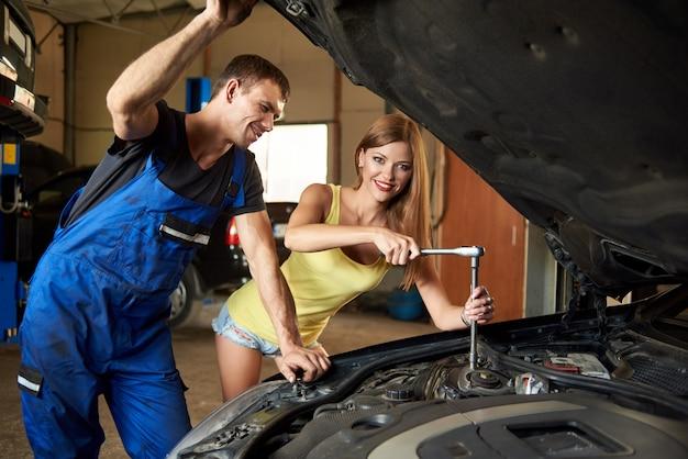 Chica reparando el auto con una llave Foto Premium