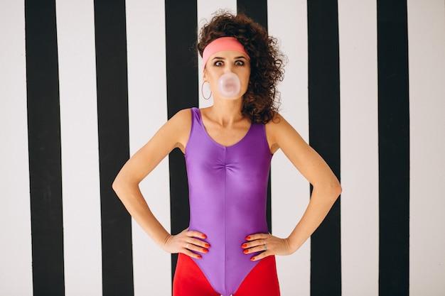 Chica retro soplando burbujas con chicle Foto gratis
