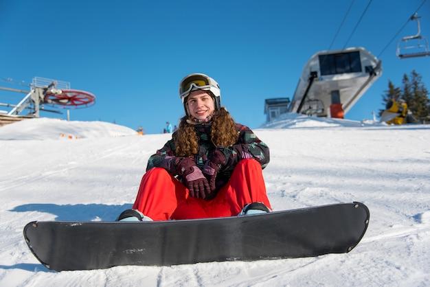 Chica rizada sentada con snowboard en la nieve cerca de remonte Foto Premium