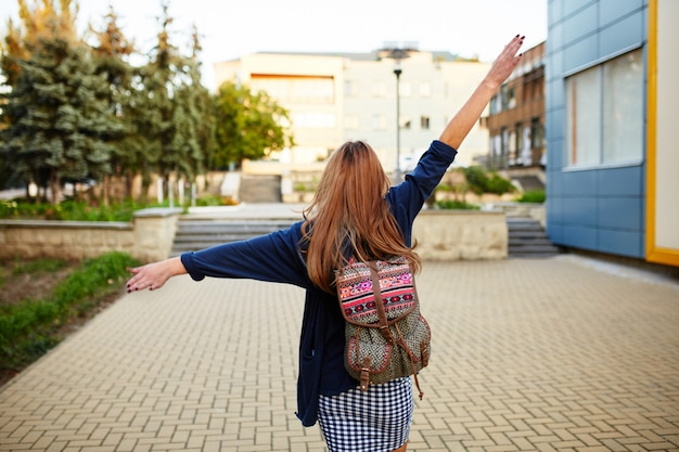 Chica robusta con una mochila caminando por la calle Foto gratis