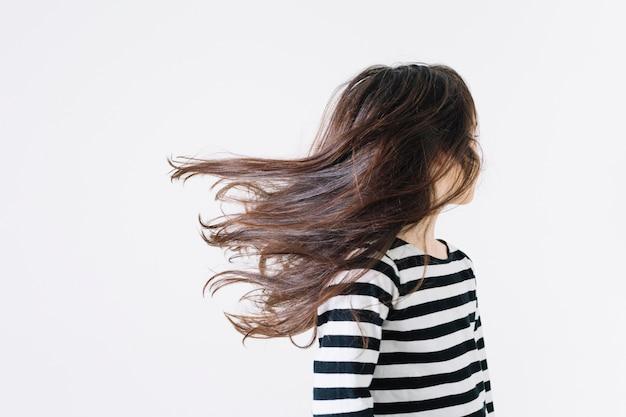 Chica sin rostro sacudiendo el cabello Foto gratis
