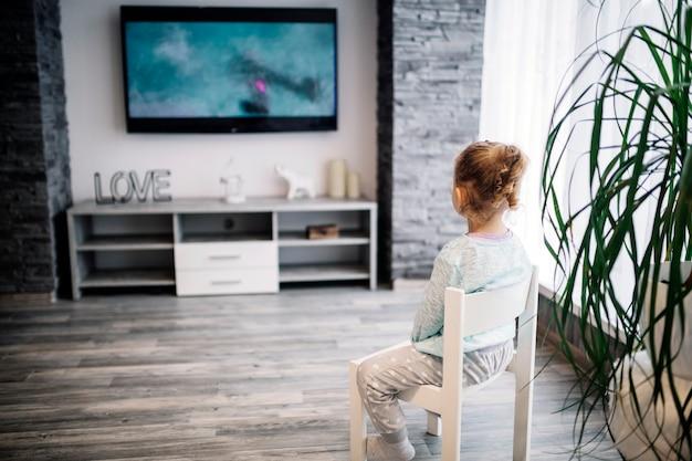 Chica sin rostro viendo la televisión Foto gratis