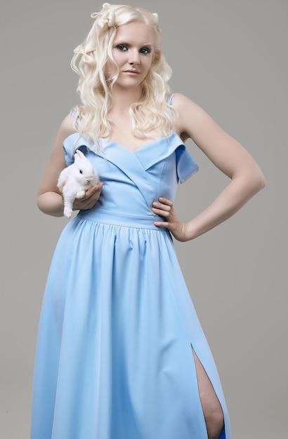 Chica rubia albina en elegante vestido posando con lindo conejito Foto Premium