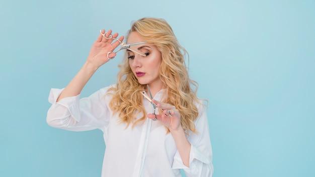Chica rubia cortándose el pelo Foto gratis