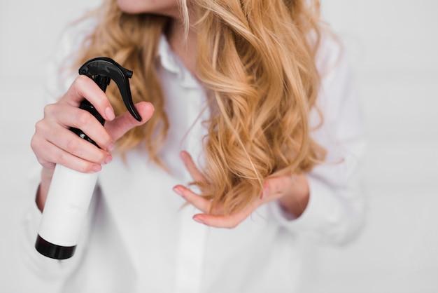 Chica rubia cuidándose el pelo Foto gratis