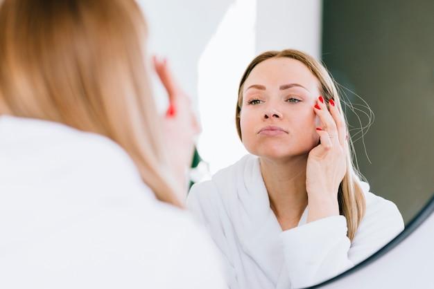 Chica rubia echándose crema en la cara | Foto Gratis