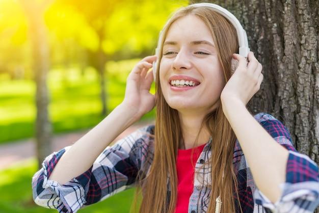 Chica rubia escuchando música con auriculares Foto gratis