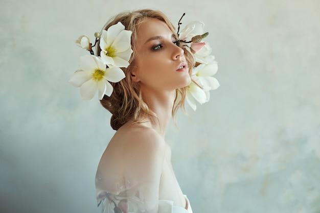 Chica rubia con flores cerca de la cara Foto Premium