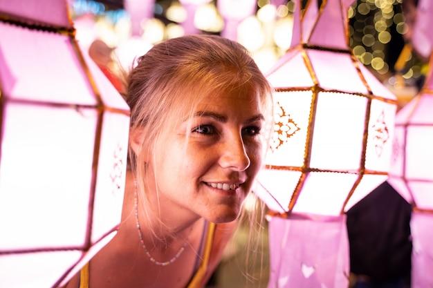 Chica rubia iluminada por faroles chinos en la noche Foto gratis