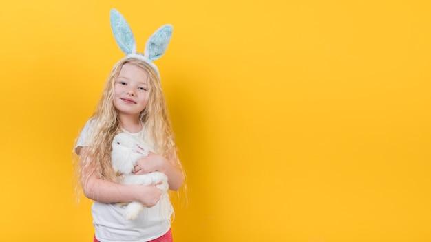 Chica rubia en orejas de conejo con conejo Foto gratis