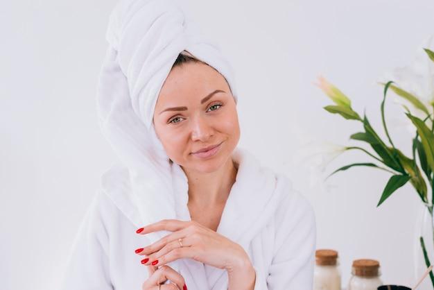 Chica rubia posando en el baño con albornoz Foto gratis