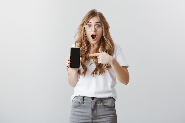 Chica rubia sorprendida y emocionada con gafas apuntando con el dedo en la pantalla del teléfono móvil, mostrando la aplicación Foto gratis