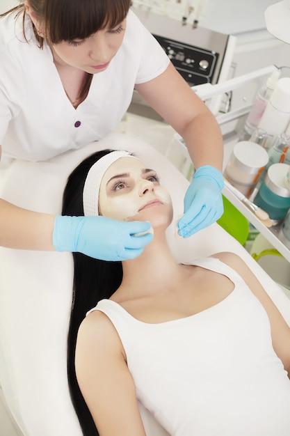 Chica en el salón de spa. esteticista aplicando polvo cosmético blanco Foto Premium
